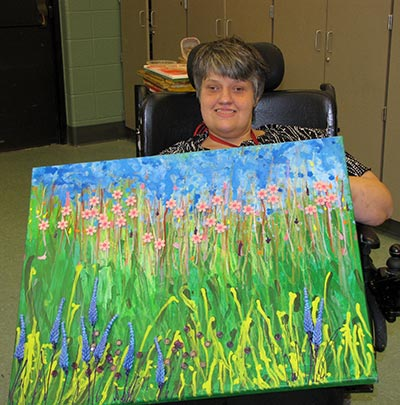 Lisa Thacker holding her a colorful art piece that she painted.