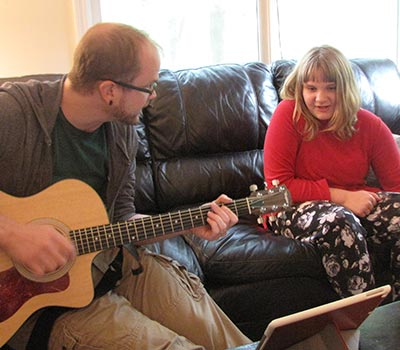 Cassidy happily singing while Noble therapist plays guitar.