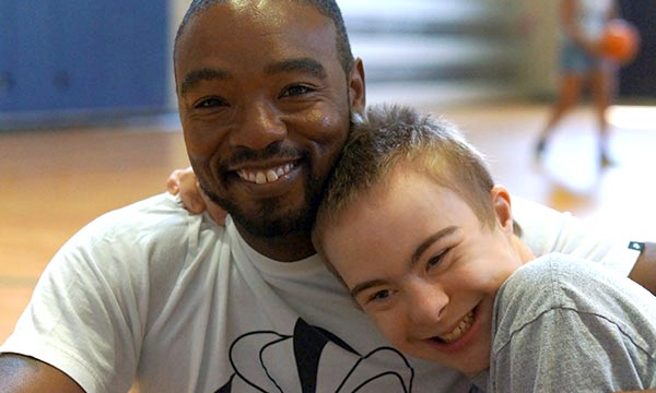 Smiling boy with Downs hugging volunteer on basketball court