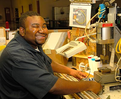 Noble participant smiling while working with factory machinery.