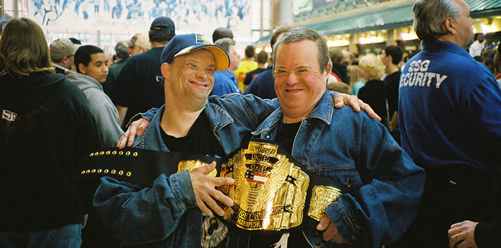 Two Noble participants smile and laugh while holding a large championship wrestling belt.