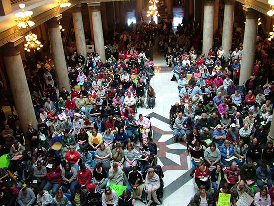 Large crowd of disabled individuals as seen from above in a large columned room.