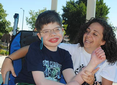 Young boy with disabilities smiling while being hugged by a smiling woman.