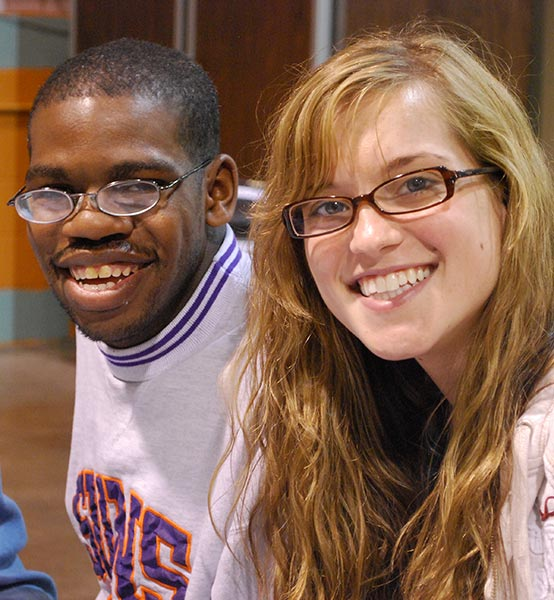 Marian College student smiles with one of our Noble participant.