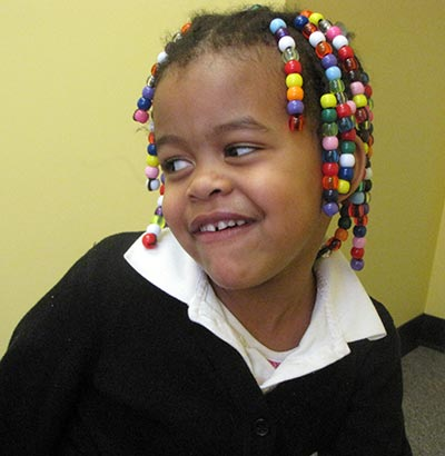 Kari smiling with beads in her hair.