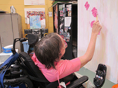 Noble participant painting on canvas from her wheelchair.