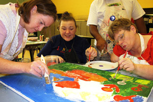 Three Noble participants paint together on a large canvas.