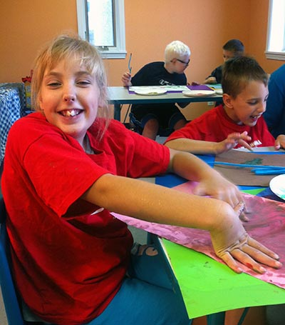 Smiling Noble participant finger painting